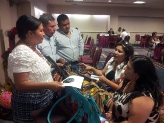 Laura Ajanel Vicente (de pie), representante de la empresa K´chubal destacó que los diseños de bolsos para mujer han logrado atraer la atención de comerciantes. Fotografía: La Voz